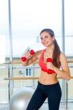Aptitud, deporte, entrenamiento y concepto de la gente - mujer que ejercita con pesas de gimnasia Imagen de archivo