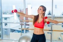 Aptitud, deporte, entrenamiento y concepto de la gente - mujer que ejercita con pesas de gimnasia Fotos de archivo