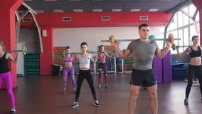 Aptitud, deporte, entrenando - grupo de mujeres y hombre con los barbells en gimnasio almacen de video