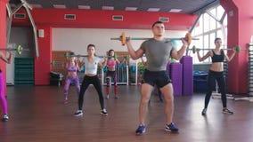 Aptitud, deporte, entrenando - grupo de mujeres y hombre con los barbells en gimnasio metrajes