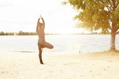 Aptitud, deporte, gente y concepto de la forma de vida - mujer joven que hace ejercicios de la yoga en la playa de la parte poste fotografía de archivo