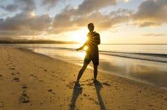 Aptitud en la playa en la salida del sol Foto de archivo