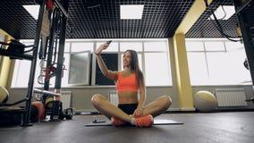 Aptitud, forma de vida, tecnología y concepto de la gente - mujer joven con el smartphone que toma el selfie en gimnasio metrajes
