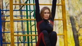 Aptitud joven Exercising modelo femenino en un prado en el parque del otoño, concepto de las actividades al aire libre de los dep Foto de archivo libre de regalías