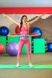 Aptitud La muchacha blanca hermosa joven en un traje rosado de los deportes hace ejercicios físicos con un aro en el centro de ap Imagen de archivo libre de regalías