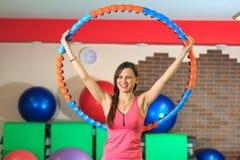 Aptitud La muchacha blanca hermosa joven en un traje rosado de los deportes hace ejercicios físicos con un aro en el centro de ap Imagen de archivo