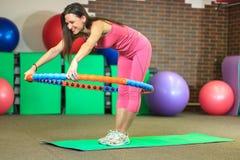 Aptitud La muchacha blanca hermosa joven en un traje rosado de los deportes hace ejercicios físicos con un aro en el centro de ap Fotografía de archivo