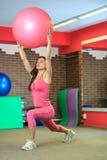 Aptitud La muchacha blanca hermosa joven en un traje rosado de los deportes hace ejercicios físicos con una bola rosada del ajust Fotografía de archivo