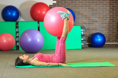 Aptitud La muchacha blanca hermosa joven en un traje rosado de los deportes hace ejercicios físicos con una bola rosada del ajust Imagen de archivo libre de regalías