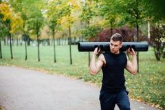Aptitud masculina que hace estocada del ejercicio con el vipr, entrenamiento de la mañana en el parque Imagenes de archivo