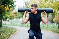 Aptitud masculina que hace estocada del ejercicio con el vipr, entrenamiento de la mañana en el parque Foto de archivo libre de regalías