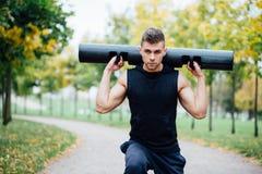 Aptitud masculina que hace estocada del ejercicio con el vipr, entrenamiento de la mañana en el parque Imagen de archivo