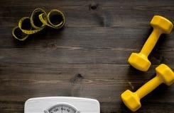 Aptitud para el peso perdidoso Báscula de baño, cinta métrica y pesa de gimnasia en copyspace de madera de la opinión superior de Fotografía de archivo