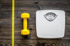Aptitud para el peso perdidoso Báscula de baño, cinta métrica y pesa de gimnasia en la opinión superior del fondo de madera Fotografía de archivo libre de regalías