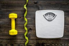 Aptitud para el peso perdidoso Báscula de baño, cinta métrica y pesa de gimnasia en la opinión superior del fondo de madera Fotos de archivo