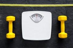 Aptitud para el peso perdidoso Báscula de baño, cinta métrica y pesa de gimnasia en la opinión superior del fondo negro Fotos de archivo