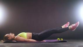 Aptitud practicante Mujer hermosa en el entrenamiento de la ropa de los deportes para abdominal en estudio almacen de video