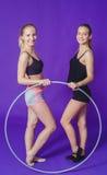 Aptitud y concepto del gimnasio - dos mujeres deportivas jovenes que sonríen con el aro del hula en el gimnasio En un fondo azul Foto de archivo