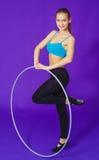 Aptitud y concepto del gimnasio - mujer deportiva joven con el aro del hula en el gimnasio En un fondo azul Fotografía de archivo