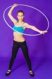Aptitud y concepto del gimnasio - mujer deportiva joven con el aro del hula en el gimnasio En un fondo azul Fotos de archivo