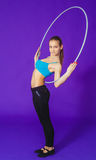 Aptitud y concepto del gimnasio - mujer deportiva joven con el aro del hula en el gimnasio En un fondo azul Imágenes de archivo libres de regalías