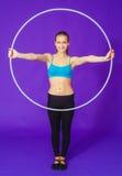 Aptitud y concepto del gimnasio - mujer deportiva joven con el aro del hula en el gimnasio En un fondo azul Foto de archivo
