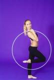 Aptitud y concepto del gimnasio - mujer deportiva joven con el aro del hula en el gimnasio En un fondo azul Imagen de archivo