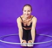 Aptitud y concepto del gimnasio - mujer deportiva joven con el aro del hula en el gimnasio En un fondo azul Imagen de archivo libre de regalías