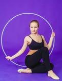 Aptitud y concepto del gimnasio - mujer deportiva joven con el aro del hula en el gimnasio En un fondo azul Fotografía de archivo libre de regalías