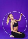Aptitud y concepto del gimnasio - mujer deportiva joven con el aro del hula en el gimnasio En un fondo azul Fotos de archivo libres de regalías