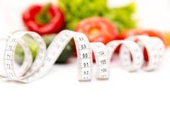 Aptitud y concepto sano de la dieta Verduras verdes frescas, cinta métrica aislada en el fondo blanco primer Foto de archivo libre de regalías