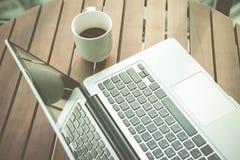 aptop και ένα φλυτζάνι του μαύρου καφέ Στοκ Φωτογραφία