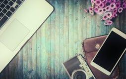 Aptop, παλαιά κάμερα και smartphone στον ξύλινο πίνακα Στοκ Εικόνες