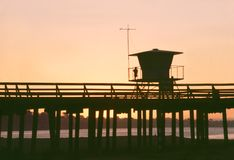 Aptos Pier. Silhouette of a pier at Aptos, California, with a boy standing by the hut Royalty Free Stock Photo