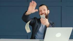Apuestas en línea que juegan el dinero que lanza del hombre feliz almacen de video