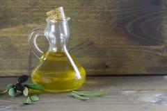 Apulian橄榄油和橄榄树枝在木桌上,意大利料理,地中海饮食 库存照片