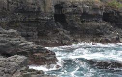 Apuntale con los acantilados y las cuevas y mar y las ondas azules Imagen de archivo libre de regalías