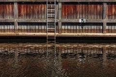 Apuntale el canal con las escaleras y la reflexión en agua en el río del danés en Klaipeda, Lituania Fotografía de archivo