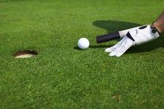 Apuntando la pelota de golf a un agujero tenga gusto del billar Fotografía de archivo
