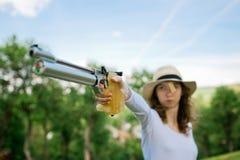 Apuntando a la pistola de sexo femenino del deporte, detalle a mano que sostiene el apret?n de 10 m foto de archivo
