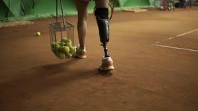 Apuntar la cantidad de las piernas del ` un s de la mujer discapacitada La muchacha delgada recoge bolas con una cesta del tenis  almacen de metraje de vídeo