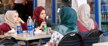 Aqaba, Giordania, il 7 marzo 2018: Le giovani signore si rilassano con le bibite in un ristorante della via al sole nel centro di fotografie stock