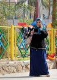 Aqaba, Jordânia, o 7 de março de 2018: Mulher muçulmana de meia idade que está em seu telefone celular, rindo do mesmo tempo imagens de stock