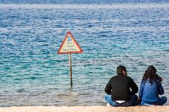 Aqaba, Jordan - January 24, 2016. Couple sitting on the shore of Red Sea with caution signboard.  stock photos