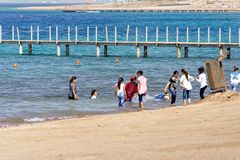 Aqaba, Jordan, March 7, 2018: Children on the beach of Aqaba, fully dressed in the sea bathing and playing stock images