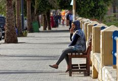 Aqaba, Jordan, March 7, 2018: Muslim young woman sitting on a bench on the beach promenade of Aqaba talking on her mobile phone Stock Image