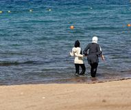 Aqaba, Jordan, March 8, 2018: Two fully clothed Muslim ladies wading through the shallow waters of the Gulf of Aqaba next to the b. Each to refresh themselves in Stock Photos