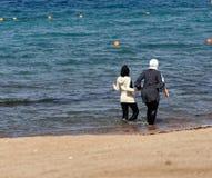 Aqaba, Jordanien, am 8. März 2018: Zwei völlig gekleidete moslemische Damen, die durch das seichte Wasser des Golfs von Akaba nah stockfotos