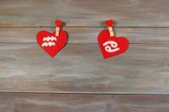 Aquário e câncer sinais do zodíaco e do coração backg de madeira foto de stock royalty free