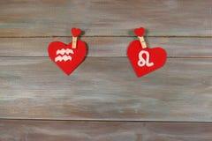 Aquário e o leão sinais do zodíaco e do coração CCB de madeira imagem de stock royalty free